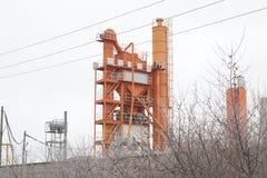 Stromleitung vor orange mischendem Block der Asphaltanlage Stockfoto