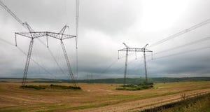 Stromleitungen auf dem Feld im wolkigen Wetter Stockfoto