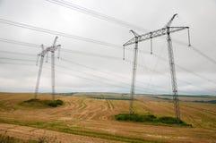 Stromleitungen auf dem Feld im wolkigen Wetter Stockbilder