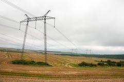 Stromleitungen auf dem Feld im wolkigen Wetter Lizenzfreies Stockfoto