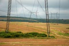 Stromleitungen auf dem Feld im wolkigen Wetter Lizenzfreie Stockfotos