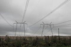 Stromleitungen auf dem Feld im wolkigen Wetter Lizenzfreies Stockbild