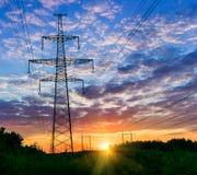 Stromleitungen auf einem bunten Sonnenaufgang, Starkstromleitungen gegen Himmel bei Sonnenaufgang Stockfotos