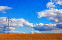 Stromleitungen, die über ein Weizenfeld mit blauem Himmel laufen Stockfotos