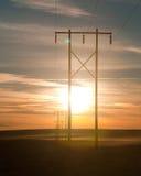 Stromleitungen führen in den Sonnenuntergang Stockbilder