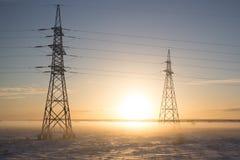 Stromleitungen im Nebel im Winter auf Sonnenuntergang lizenzfreie stockfotos