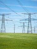 Stromleitungen mit blauem Himmel und grünem Gras Lizenzfreie Stockfotos