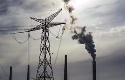 Stromleitungen- und Kraftwerkstapel am Hintergrund Stockbilder