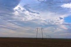 Stromleitungen und schwere Wolken auf flachem Ackerland am Vorfrühling Lizenzfreie Stockbilder