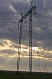 Stromleitungen und schwere Wolken auf flachem Ackerland am Vorfrühling Lizenzfreies Stockfoto