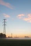 Stromleitungen während des Sonnenaufgangs Stockbild
