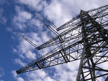Strommast. Electric pylon with the wires in front of blue sky with white clouds stock image