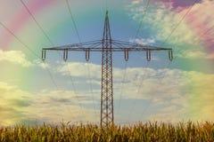 Strommast auf einem Maisfeld und Regenbogen im Himmel stockfoto
