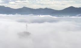 Strommast in der nebeligen Landschaft des Nebels Lizenzfreies Stockfoto