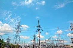 Strommast, Stromturmstation mit bewölktem und Sonne über blauem Himmel Lizenzfreie Stockfotos