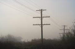 Strommaste, die in der Stille des früher Morgen-Nebels stehen Stockfoto
