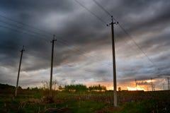 Strommaste mit bewölktem Himmel Stockbild