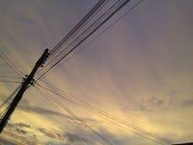 Strommaste und schönes Himmellicht des Sonnenuntergangs stockbild