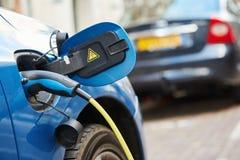 Stromversorgung verstopfte in ein Elektroauto während der Aufladung Stockfoto