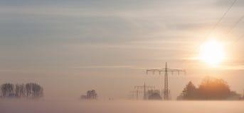 Stromversorgungsversorgungslinien im Nebel während des Winters lizenzfreie stockfotos