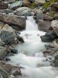 Stromy kamienisty strumienia łóżko Alpejski strumyk Zamazane fala biega nad głazami i kamieniami strumień, wysoka woda równa po d obrazy royalty free