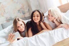 strona Młode kobiety kłama na łóżku wpólnie w domu bierze selfie na smartphone radosnym obrazy stock