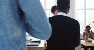Strona rozwesela on w górę rywalizuje szczęśliwego młodego pomyślnego męskiego szefa odprowadzenie wzdłuż loft biura z teczką, ko zbiory