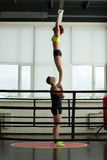 Strong acrobat holding his slender partner in gym Stock Photography