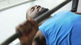 Strong African American man doing barbell bench press exercise, workout in gym. Stock footage stock video footage