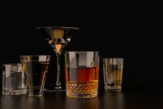 Strong alcoholic drinks, glasses and glasses, in the presence of whiskey, vodka, rum, tequila, brandy, cognac. on a dark old backg. Strong alcoholic beverages royalty free stock image