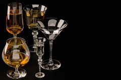 A set of strong alcoholic beverages in glasses, in the presence of whiskey, vodka, rum, brandy, tequila, on a dark background royalty free stock image