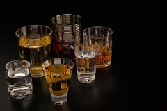 A set of strong alcoholic beverages in glasses, in the presence of whiskey, vodka, rum, brandy, tequila, on a dark background stock photo
