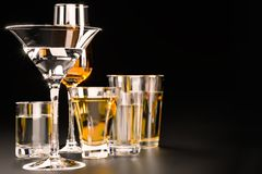 A set of strong alcoholic beverages in glasses, in the presence of whiskey, vodka, rum, brandy, tequila, on a dark background royalty free stock photography