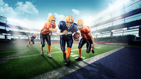 Strong american football players on green grass. Professional american football players in the action on stadium Royalty Free Stock Photo