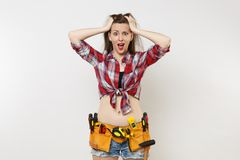 Strong angry handyman woman in plaid top shirt, denim shorts, kit tools belt full of variety useful instruments isolated. On white background. Female doing male royalty free stock photos