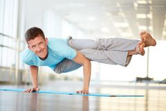 Strong arms. Portrait of young man doing physical exercise in gym Stock Images