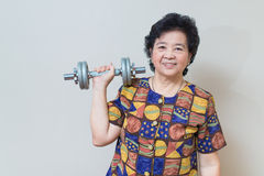 Strong Asian senior woman lifting weights, in studio shot, speci Royalty Free Stock Images