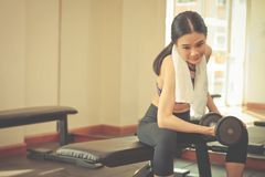 Strong skinny woman is lifting dumbbell in fitness Royalty Free Stock Image
