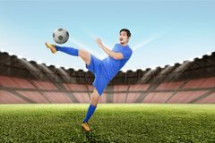 Strong asian soccer player kick the ball. On the field Stock Image