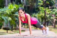 Strong Asian woman doing sport push-up in park Royalty Free Stock Photography