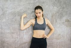 Strong asian woman posture standing and lifting up her arms and exercises muscle at gym royalty free stock photos