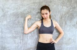 Strong asian female posture standing and lifting up her arms and exercises muscle at gym. Strong asian woman posture standing and lifting up her arms and royalty free stock photo