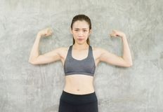 Strong asian woman posture standing and lifting up her arms and exercises muscle at gym royalty free stock image