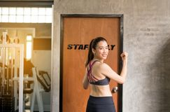Strong asian woman posture standing and lifting up her arms and exercises muscle at gym stock image