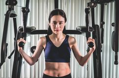 Strong asian woman training on fitness gym machine. Strong asian woman is training on fitness gym machine Royalty Free Stock Photos