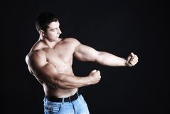 Strong athlete. Young man athlete with perfect body at black background Stock Image