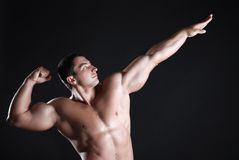 Strong athlete. Young man athlete with perfect body at black background Royalty Free Stock Photography