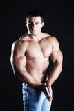 Strong athlete. Young man athlete with perfect body at black background Stock Photos