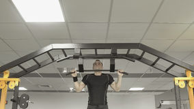 Strong athlete man doing exercises on the horizontal bar in gym Royalty Free Stock Photo