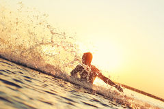 Strong athlete splashing in the water at sunset. Strong man splashing in the water at sunset Royalty Free Stock Photo